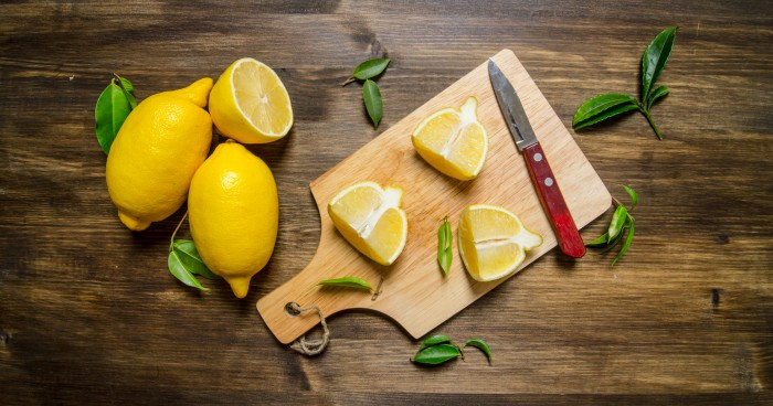 Sliced lemon on the board with leaves.